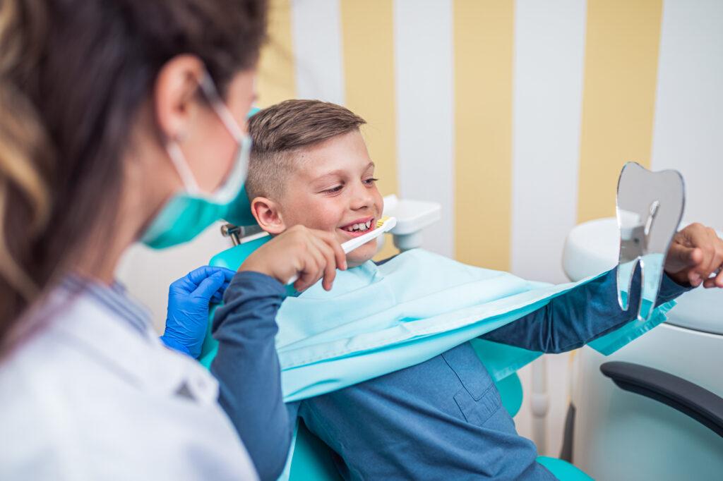 Dečiji stomatolog i decak sa četkicom za zube
